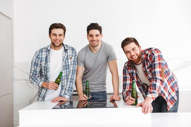 Retrato de três amigos sorridentes do sexo masculino comemorando em pé com garrafas de cerveja dentro de casa