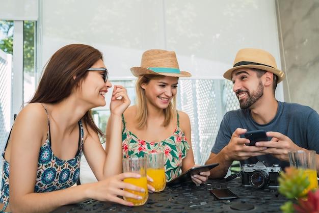 Retrato de três amigos viajantes passando um tempo e organizando sua viagem no hotel. conceito de viagens e estilo de vida.