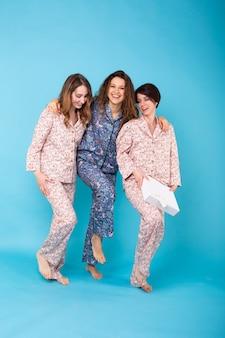 Retrato de três belas garotas de pijama colorido, se divertindo durante a festa do pijama isolada sobre uma parede azul. festa do pijama e conceito de despedida de solteiro