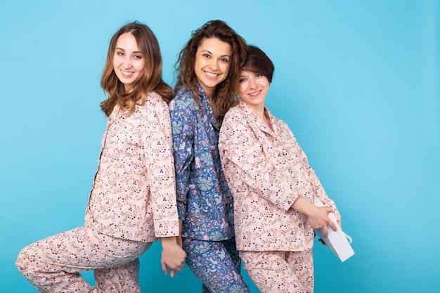 Retrato de três belas garotas de pijama colorido, se divertindo durante a festa do pijama isolado sobre fundo azul. festa do pijama e conceito de despedida de solteiro