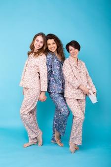 Retrato de três belas jovens de pijama colorido se divertindo durante a festa do pijama