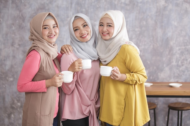 Retrato de três belas mulheres muçulmanas em pé e sorrindo, segurando xícaras de café