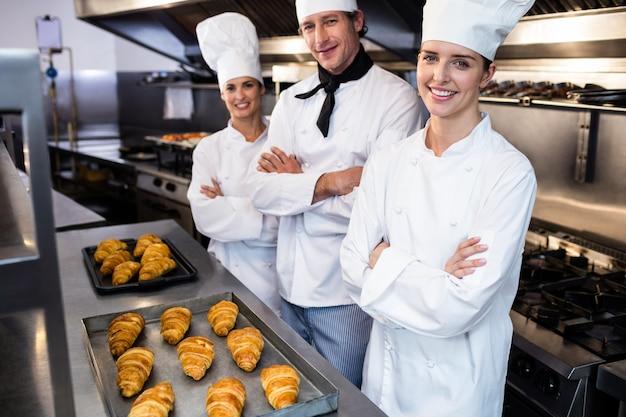 Retrato de três chefs na cozinha comercial