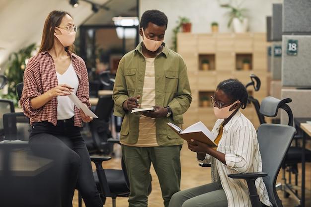 Retrato de três empresários contemporâneos usando máscaras enquanto discutia um projeto de trabalho em um escritório moderno de pós-pandemia