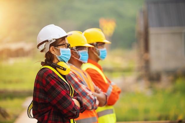 Retrato de três engenheiros em um canteiro de obras usando máscaras, tailândia