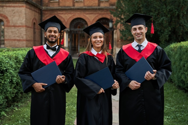 Retrato de três estudantes internacionais femininos e masculinos com diplomas, celebrando a formatura no campus da universidade.