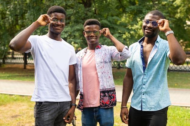 Retrato de três homens alegres africanos em copos no verão no parque