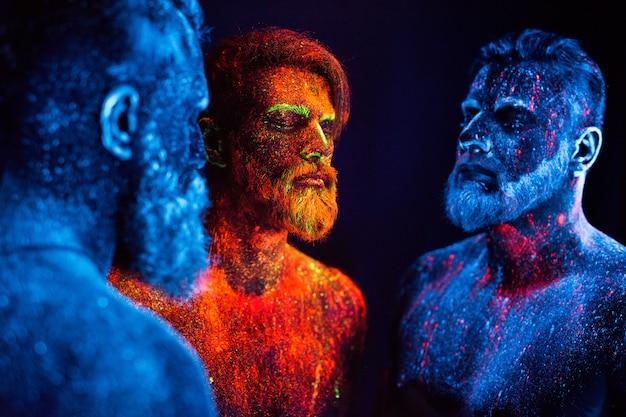 Retrato de três homens barbudos pintados em pó fluorescente.