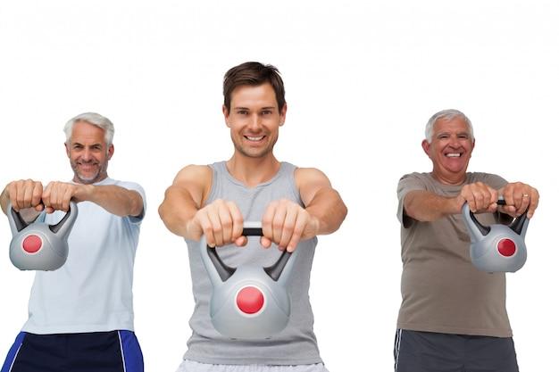 Retrato de três homens que exercitam com sinos de chaleira