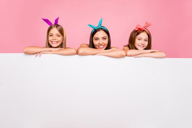 Retrato de três irmãos encantadores com tiaras brilhantes, colocando as mãos em padrão isolado sobre fundo rosa