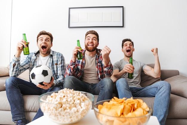 Retrato de três jovens alegres assistindo futebol enquanto estão sentados em casa, bebendo cerveja e comendo lanches