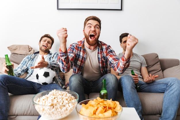Retrato de três jovens animados assistindo futebol enquanto estão sentados em casa, bebendo cerveja e comendo lanches
