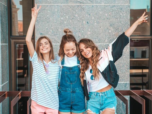 Retrato de três jovens bonitas garotas hipster sorridente em roupas da moda no verão. mulheres despreocupadas sexy, posando na rua. modelos positivos se divertindo. abraçando e levantando as mãos