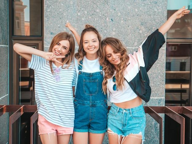 Retrato de três jovens bonitas garotas hipster sorridente em roupas da moda no verão. mulheres despreocupadas sexy, posando na rua. modelos positivos se divertindo. eles levantam as mãos