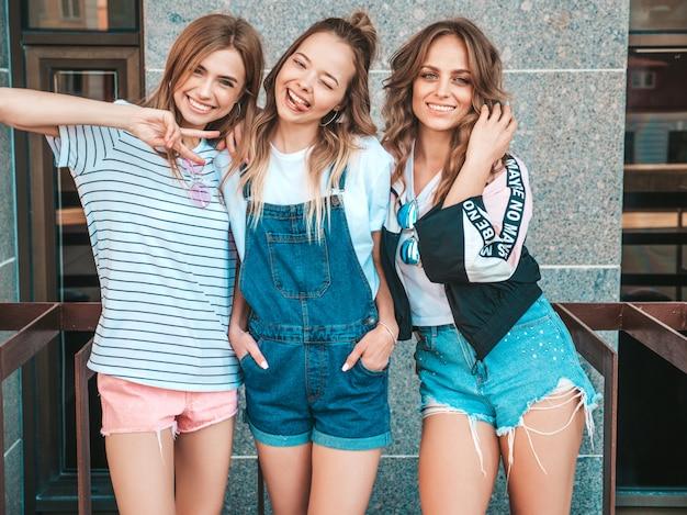 Retrato de três jovens bonitas garotas hipster sorridente em roupas da moda no verão. mulheres despreocupadas sexy, posando na rua. modelos positivos se divertindo. eles mostram a língua e o sinal de paz