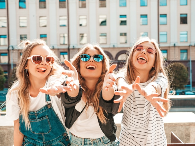 Retrato de três jovens bonitas garotas hipster sorridente em roupas da moda no verão. mulheres despreocupadas sexy, posando na rua. modelos positivos se divertindo. eles puxam as mãos para a câmera