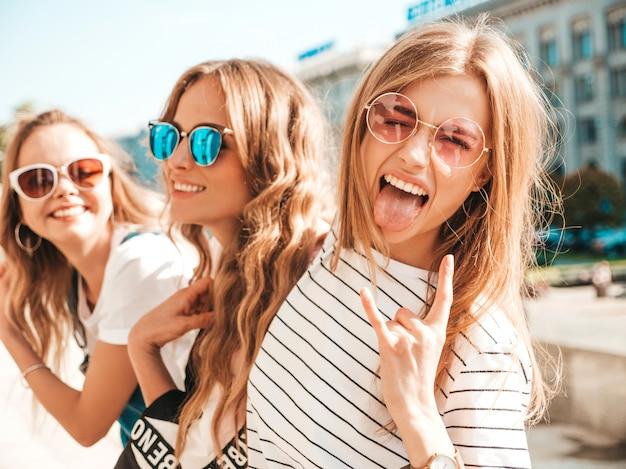 Retrato de três jovens bonitas garotas hipster sorridente em roupas da moda no verão. mulheres despreocupadas sexy, posando na rua. modelos positivos, se divertindo em óculos de sol. mostra o sinal de rock and roll