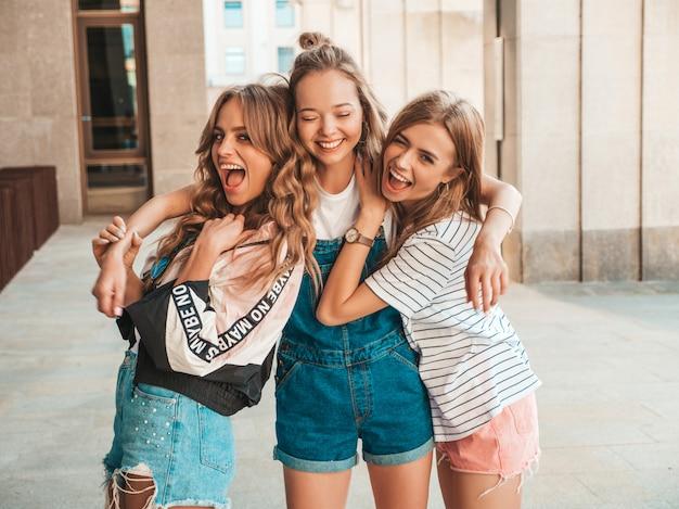 Retrato de três jovens bonitas garotas hipster sorridente em roupas da moda no verão. mulheres despreocupadas sexy, posando na rua. modelos positivos, se divertindo.