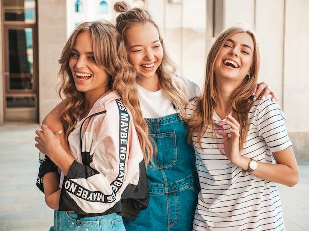 Retrato de três jovens bonitas garotas hipster sorridente em roupas da moda no verão. mulheres despreocupadas sexy, posando na rua. modelos positivos, se divertindo