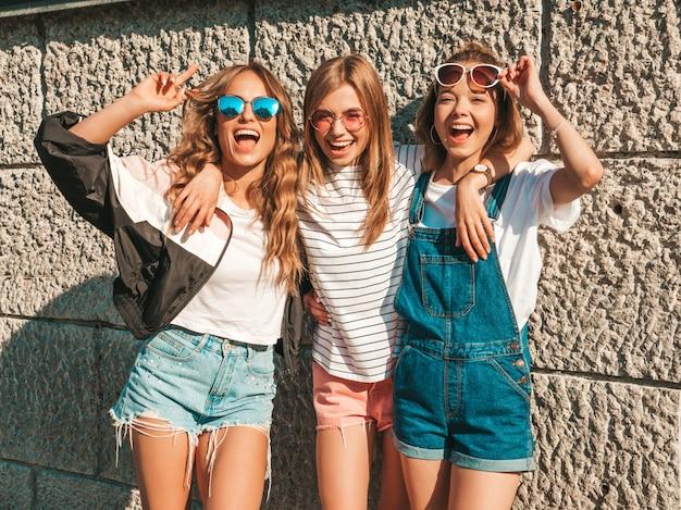 Retrato de três jovens bonitas garotas hipster sorridente em roupas da moda no verão. mulheres despreocupadas sexy posando perto da parede na rua. modelos positivos se divertindo em óculos de sol