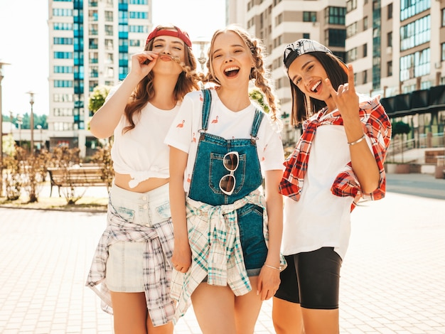 Retrato de três jovens bonitas garotas hipster sorridente em roupas da moda verão