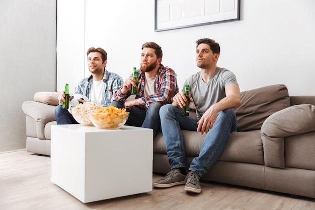 Retrato de três jovens concentrados assistindo futebol enquanto estão sentados em casa, bebendo cerveja e comendo lanches