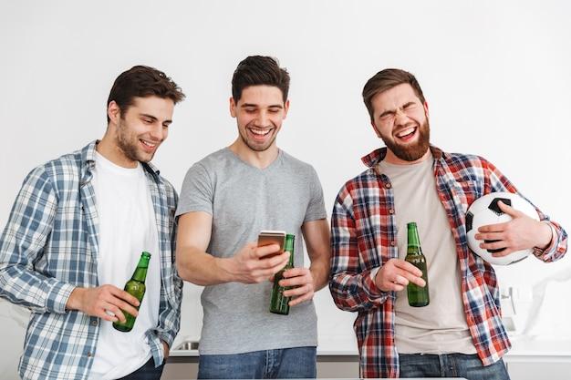 Retrato de três jovens felizes bebendo cerveja e assistindo futebol no celular em casa