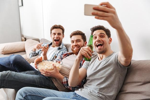 Retrato de três jovens felizes tirando uma selfie sentado em casa com cerveja e petiscos dentro de casa