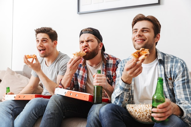Retrato de três jovens solteiros comendo pizza com prazer, enquanto assistia a uma partida de futebol na tv