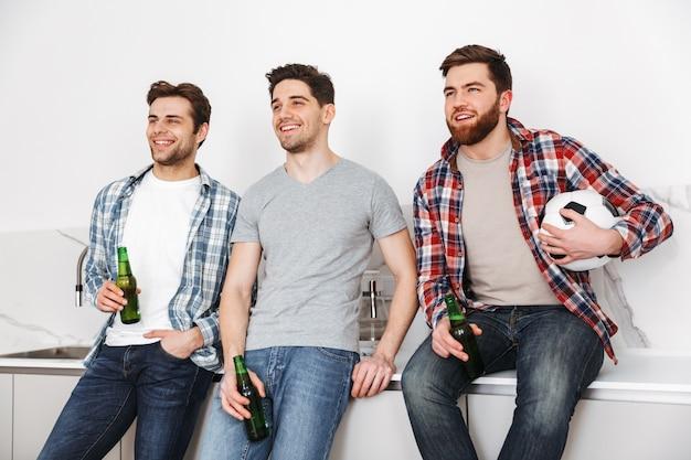 Retrato de três jovens sorridentes, bebendo cerveja e assistindo futebol em casa