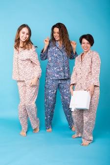 Retrato de três lindas garotas de pijama colorido se divertindo durante a festa do pijama