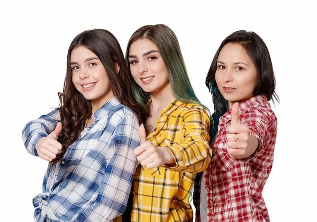 Retrato de três lindas jovens mulheres felizes sorrindo alegremente, mostrando os polegares isolados no branco
