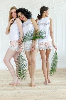 Retrato de três lindas mulheres jovens multirraciais com diferentes tipos de pele.
