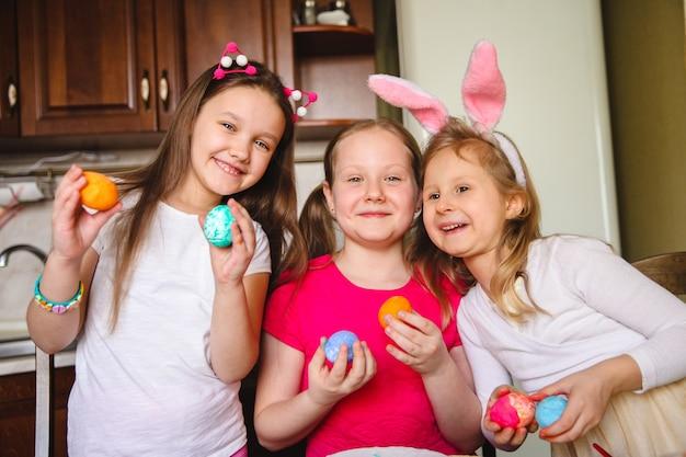 Retrato de três meninas em casa na cozinha com ovos de páscoa pintados por elas nas mãos.