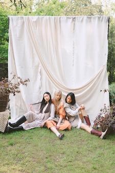 Retrato de três mulheres bonitas no jardim, sentado no chão durante o dia.