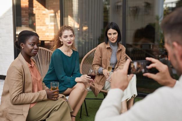 Retrato de três mulheres elegantes posando para a foto e sorrindo para a câmera enquanto desfruta de uma festa ao ar livre no terraço.