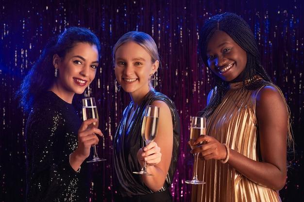 Retrato de três mulheres segurando taças de champanhe e sorrindo para a câmera enquanto posam contra um fundo cintilante na festa