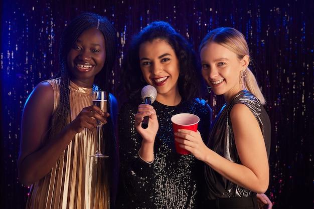 Retrato de três mulheres segurando taças de champanhe e sorrindo para a câmera enquanto posam em um fundo cintilante na festa de karaokê