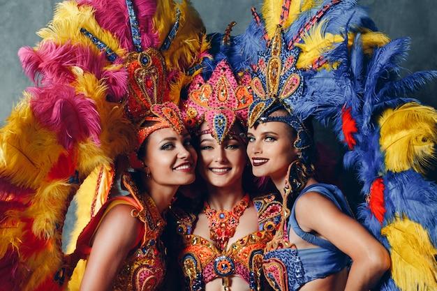 Retrato de três mulheres sorrindo em traje de carnaval samba brasileiro com plumagem de penas coloridas.