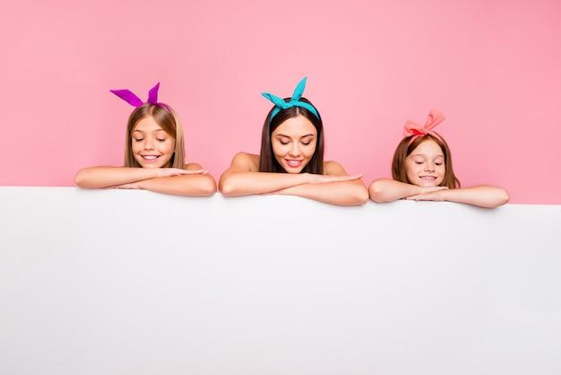 Retrato de três pessoas curiosas com corte de cabelo loiro usando tiaras, colocando as mãos em quadro branco puro isolado sobre fundo rosa