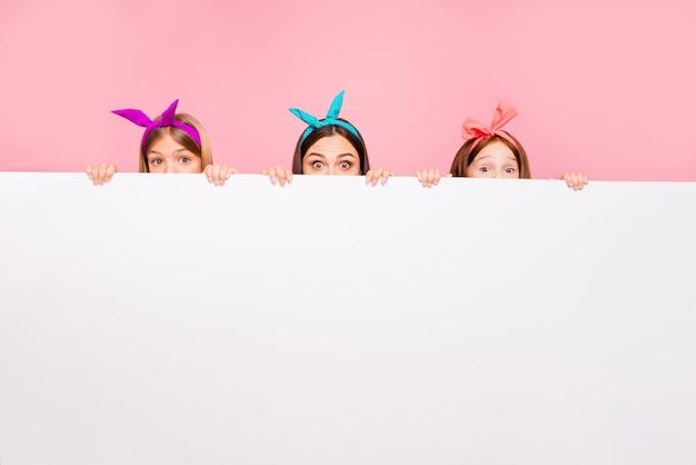 Retrato de três pessoas engraçadas se escondendo atrás de um padrão puro usando tiaras brilhantes isoladas sobre um fundo rosa
