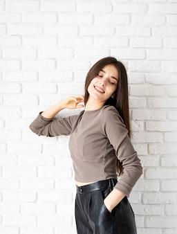 Retrato de três quartos de comprimento de uma linda mulher morena sorridente com cabelo comprido, vestindo uma camisa marrom e shorts de couro preto, sobre fundo de parede de tijolo branco