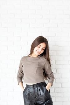Retrato de três quartos de comprimento de uma linda mulher morena sorridente com cabelos longos, vestindo camisa marrom e shorts de couro preto, sobre fundo de parede de tijolo branco, mãos nos bolsos