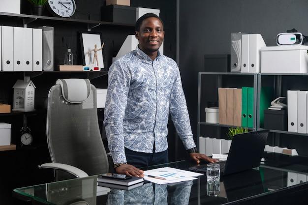 Retrato de três quartos de comprimento jovem empresário preto em pé perto da mesa no escritório
