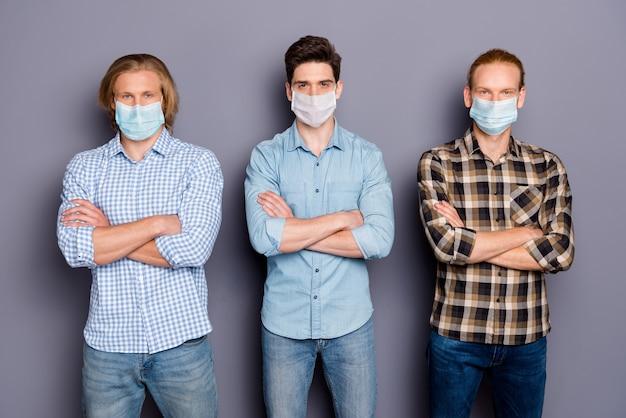 Retrato de três rapazes sérios, melhor amigo colega corona vírus equipe de luta de braços cruzados, usa máscara médica isolada sobre fundo cinza pastel