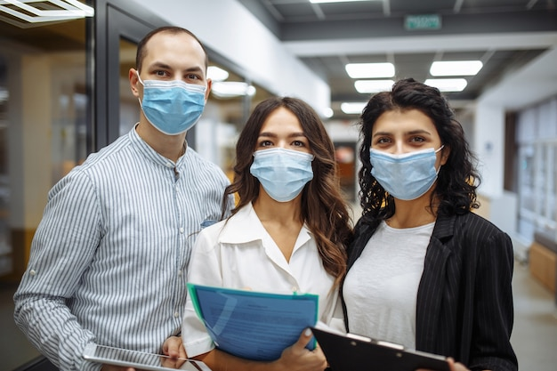 Retrato de três trabalhadores de escritório usando máscaras médicas, discutindo negócios e perspectivas futuras.