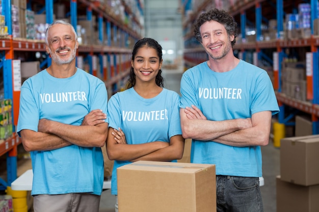 Retrato de três voluntários felizes em pé com os braços cruzados