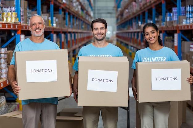 Retrato de três voluntários segurando uma caixa de doações