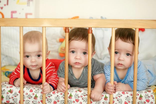 Retrato de trigêmeos recém-nascidos na cama