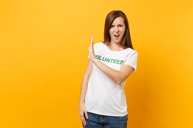 Retrato de triste chateado jovem chocado em camiseta branca com voluntário de título verde de inscrição escrita isolado em fundo amarelo. ajuda de assistência gratuita voluntária, conceito de trabalho de graça de caridade.